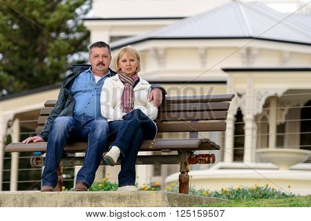 Senior couple in their late fifties sitting on the bench in Australian countryside