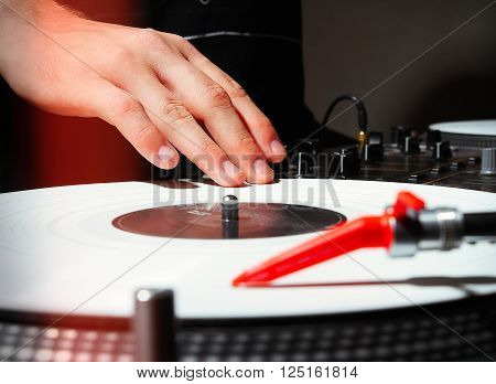 Hand of a DJ playing music on turntable with white vinyl record in dark studio or nightclub. Professional analog sound equipment