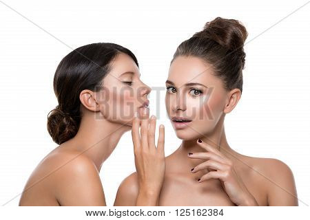 Two beautiful young women with perfect skin gossiping about somthing. Isolated over white background. Beauty shot. Copy space.