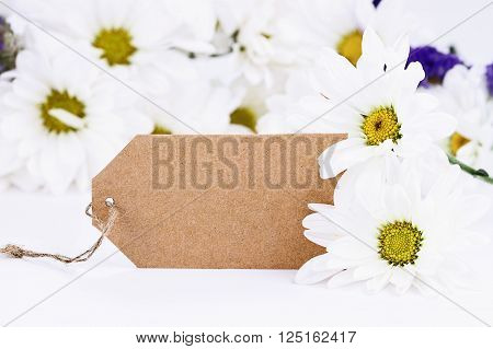 Blank card and daisies with room for your text. Extreme shallow depth of field with selective focus on card.