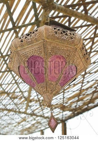 Old rusty vintage metallic arabic lamp hanging on the ceiling of a moroccan riad