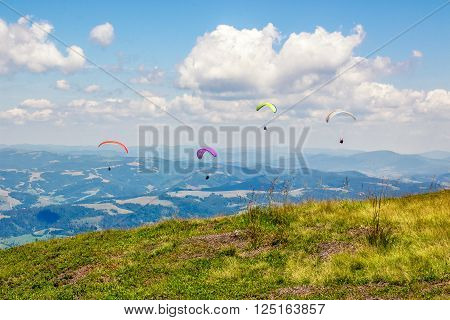 Four persones skydiving  flying over the mountains. parachute extreme sport