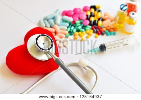 Heart, stethoscope, drugs and syringe, heart healthy concept