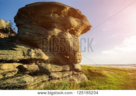The stone remnants of old sanctuary near the Big Allaki lake in Southern Urals Russia. Selective focus at the stone. Summer sunny landscape. Soft focus applied