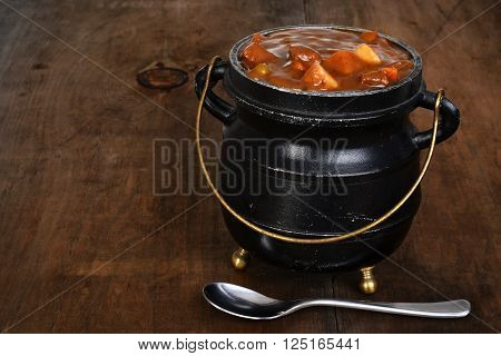 beef stew in black pot with a spoon