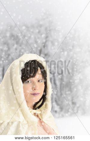 portrait of woman wearing cloak in snowing forest