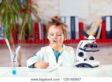 surprised kid boy writing notes after experiment in school lab