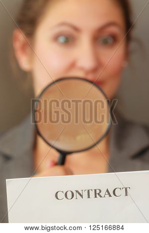 Contracts and agreements concept. Adult beauty woman in jacket holding showing contract. Close up portrait of person with loupe studying agreement.