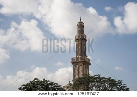 An old mosque minaret against cloud background.