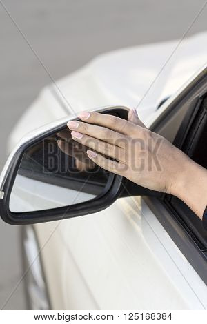 girl on a white machine adjusts the rearview mirror