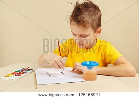Beginner artist in a yellow shirt painting colors
