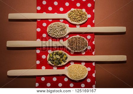 Seeds on wooden spoons which are lying at the red napkin - sesame, linseed, pumpkin and sunflower seeds, green lentils
