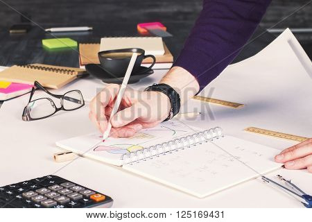 Businessman drawing business charts in copybook on desktop with office tools and coffee