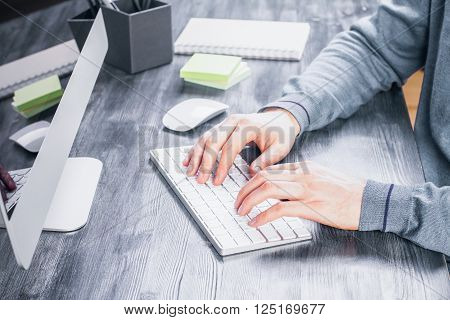 Sideview of desk with male hands typing on keyboard computer screen and other items
