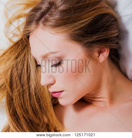 Close up portrait of young blonde girl lying on the bed, eyes closed, sleeping, boudoir beauty concept, high angle view