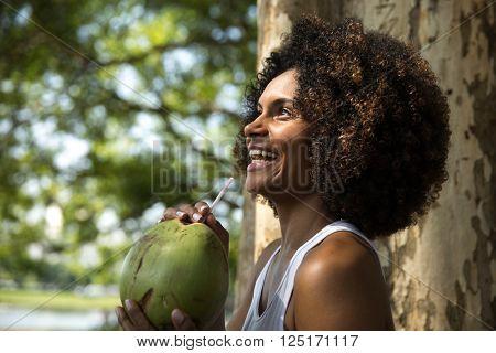 Brazilian woman drinking coconut water in the park