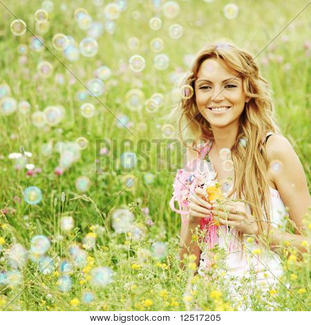 Blonde starts soap bubbles in a green field