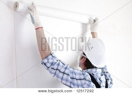 worker attaching wallpaper