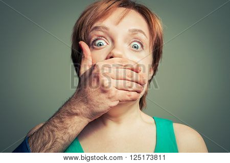 male hand shutting up the woman closeup