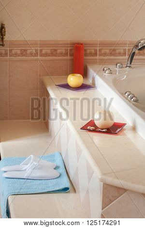 Comfy spa-style slippers on blue towel besides the jacuzzi bathtub in home bathroom.