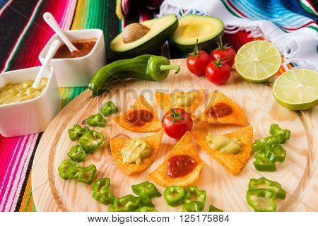 Nachos chips and vegetables on a chopping board over a colored poncho
