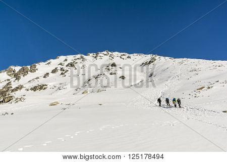Zakopane Poland - March 28 2016: Hikers on the approach to the summit in the Polish Tatra mountains in winter conditions.