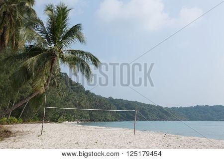 Beach volleyball on sandy beach with blue sky
