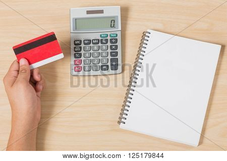 hand holding credit card and put calculator and notebook on wood table ** Note: Visible grain at 100%, best at smaller sizes