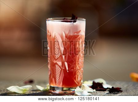 Singapore Sling in the sunlight with rose petals. Shallow dof