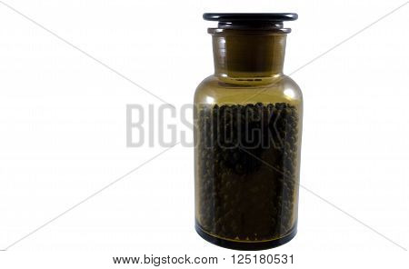 Dried juniper berry in a glass jar isolated on whitepicture from the Northof Sweden