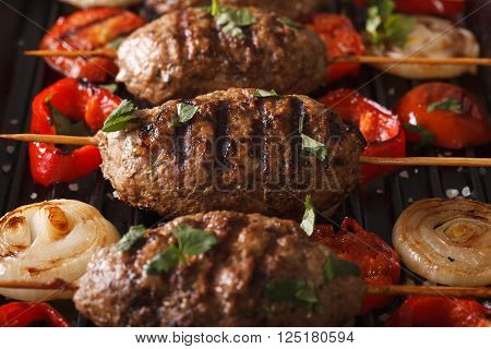 Kyufta Kebabs With Vegetables Macro On A Grill Pan. Horizontal