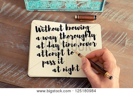 Retro effect and toned image of a woman hand writing on a notebook. Handwritten quote Without knowing a way thoroughly at day time, never attempt to pass it at night as inspirational concept image