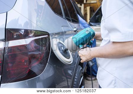 Image of worker using a polish machine to polish the car body in the garage