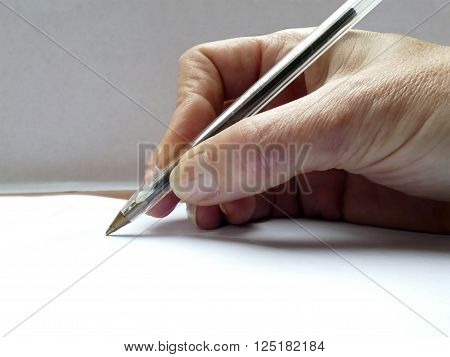 Hand with pen signing paper with undiscernible text
