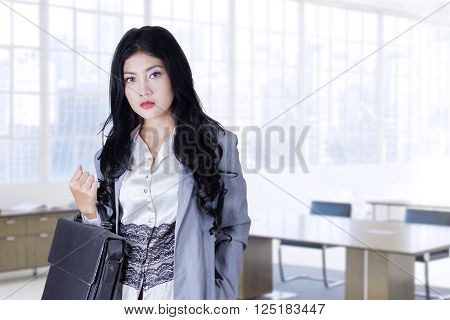 Photo of a young Asian businesswoman standing in the office while holding a briefcase