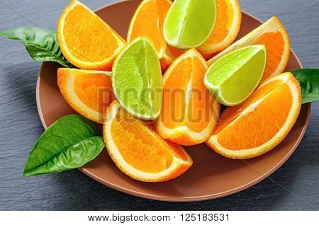 Orange and lime sliced segments  with green leaves on brown plate, black slate stone