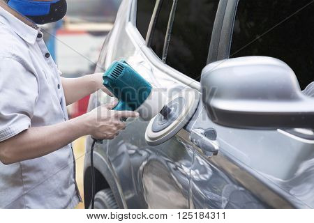 Close up of a male worker using a polisher to polish a car body in the garage
