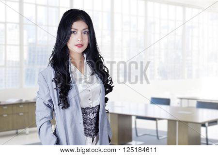 Portrait of a beautiful businesswoman with long hair standing in the office while wearing formalwear and smiling at the camera
