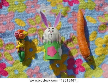 Easter bunny made of an egg shell with plasticine flowers and carrot on the flower background.