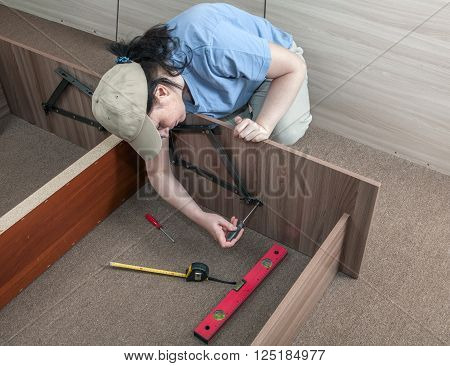 Self assembling furniture at home woman housewife putting together assemble bed frame using hand tools.