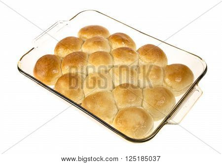 Pan of hot dinner rolls fresh from the oven in a glass pan isolated  on white.