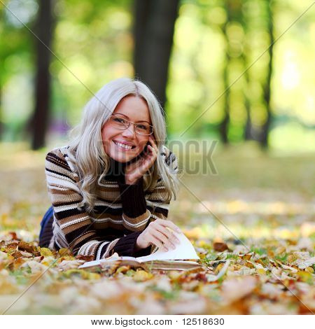 woman read the book in autumn park