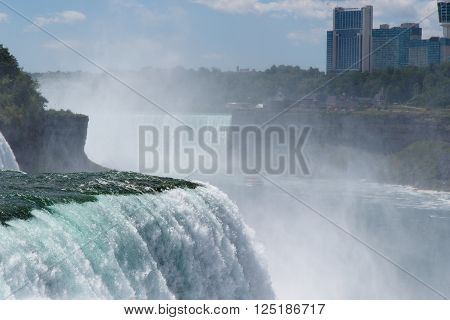 Color DSLR stock image of Niagara Falls, showing American Falls and Canadian side through the water mist and spray; horizontal with copy space for text