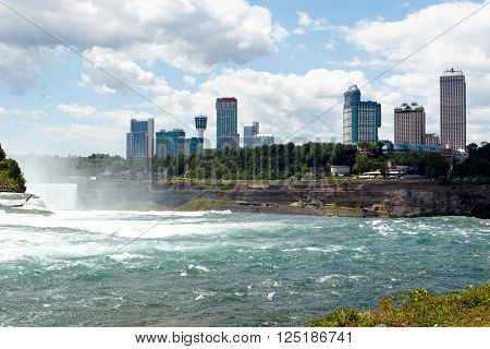wide angle image of Niagara Falls, showing American Falls and Canadian side, with casino and hotels; horizontal with copy space for text
