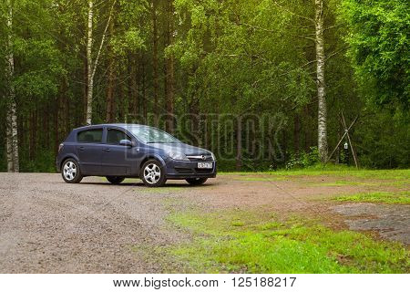 LAPPEENRANTA FINLAND - JUNE 13 2014: Summer outdoor recreation Scandinavian vacation in house on wheels. Dark-blue Opel Astra H parked on a green meadow in campsite among trees. Palvaanjarven Campsite Luumaki Lappeenranta Finland Suomi