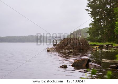 Cloudy summer day on the lake. Wooden boat pier overlooking the water and island. Area for summer camping in the woods. Palvaanjarven Campsite Lappeenranta Finland Suomi