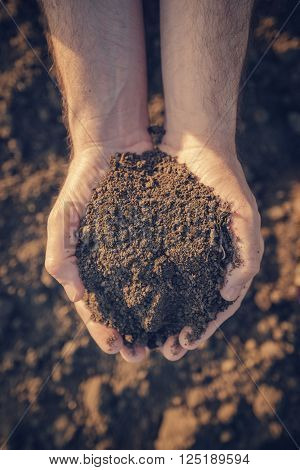 Farmer holding pile of arable soil and examining its quality on fertile agricultural land male agronomist preparing land for new seedingg season close up of hands.