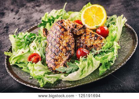 Grilled chicken breast in different variations with lettuce salad cherry tomatoes .mushrooms herbs cut lemon on a wooden board or grill pan. Traditional cuisine. Grill kitchen.