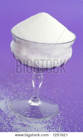Granulated Sugar In A Vintage Lavender Stemware Glass On Purple