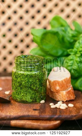 Fresh homemade Basil pesto with pine nuts in a glass jar , Basil leaf and toast on the table. Selective focus